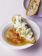 Stock Photo of Fennel soup with tomatoes served with crostini topped with fennel and manchego