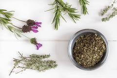 Herbs de Provence in a bowl surrounded by fresh herbs - stock photo
