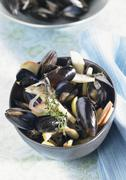 Mussels in broth with apple slices and thyme Stock Photos