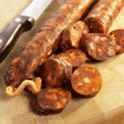 Stock Photo of Partially Sliced Spanish Chorizo on a Cutting Board