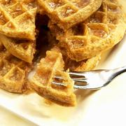 Stack of Five Grain Waffle with Organic Maple Syrup; Piece on a Fork - stock photo