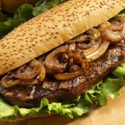 Grilled Steak and Onion Sandwich with Lettuce on a Roll - stock photo