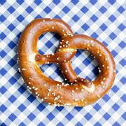 Stock Photo of A pretzel on a blue and white tablecloth