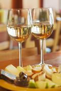 Two Glasses of White Wine with Fruit and Cheese - stock photo