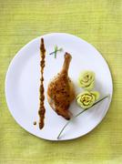Stock Photo of Duck Drumstick with Celery Flowers on a White Plate; From Above