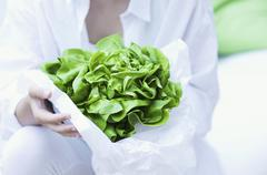 A girl holding a lettuce wrapped in paper - stock photo