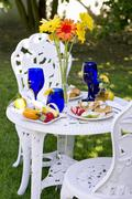 Outdoor Table Set with a Belgian Waffle Breakfast; Tall Flowers in a Vase on Stock Photos