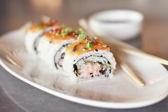 Spicy Tuna and Salmon Sushi Roll on a White Plate; Chopsticks Stock Photos