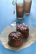 Mini chocolate cakes decorated with sugar hearts on a blue wooden table - stock photo