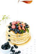 Blueberry pancakes with strawberry sorbet and maple syrup - stock photo