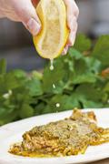 Salmon trout with a herb crust being drizzled with lemon juice Stock Photos