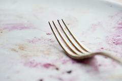 A fork on a dirty plate Stock Photos