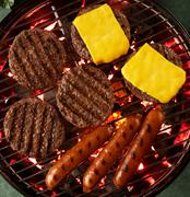 Hamburgers, Cheeseburgers and Hot Dogs on a Grill; From Above Stock Photos