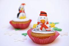 Cupcakes decorated with penguin fingurines Stock Photos