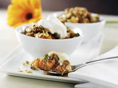 Spoonful of Apricot and Pistachio Crisp with Bowls of Crisp in Background Stock Photos