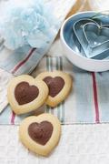 Heart-shaped biscuits and heart-shaped cutters - stock photo