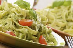 Tagliatelle with pesto, fresh basil and tomatoes Stock Photos