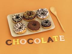 Six doughnuts and the word chocolate Stock Photos
