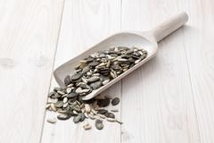 Sunflower seeds, pumpkin seeds and pine nuts on a wooden scoop - stock photo