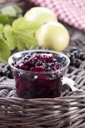 Blackcurrant and apple jam in a glass jar - stock photo