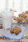 Homemade Oatmeal Cookies with a Glass of Milk; One Cookie with Bite Taken Out; - stock photo