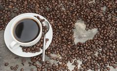 black coffee surrounded by beans with heart shaped hole, coffee lover - stock photo