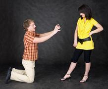 man is kneeling to the young woman - stock photo