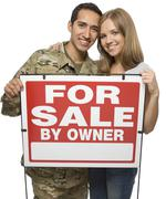 Military Couple Holding A For Sale By Owner Sign Stock Photos