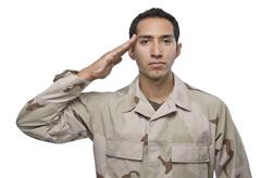 Hispanic military veteran salutes - stock photo