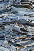 stack of different old worn blue jeans - stock photo