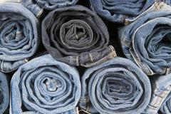 rolls of different worn blue jeans stacked - stock photo