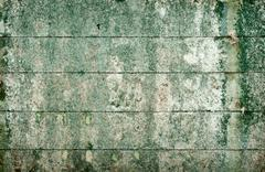 Stock Photo of green messy surface of the old wall covered with boards
