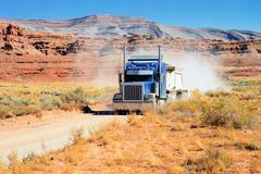 Semi-truck driving across the desert Stock Photos