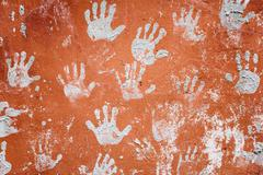Concrete red wall with prints of hands Stock Photos