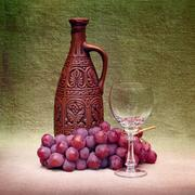 still-life with clay bottle, glass and grapes against canvas - stock photo