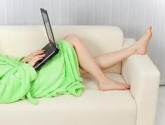 young woman and the laptop on a sofa - stock photo