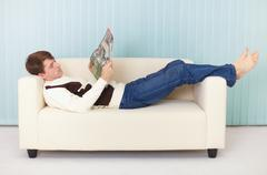 Young woman lies comfortably on sofa with a magazine Stock Photos