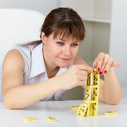 Funny woman are concentrated in building a tower with domino Stock Photos