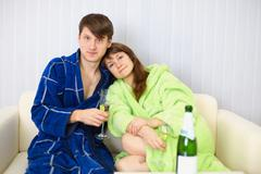 young couple in dressing gowns sitting on couch with fizz - stock photo