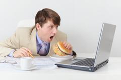 Comic clerk eats sandwich looking at screen Stock Photos