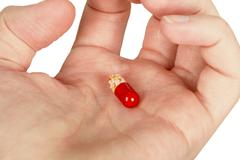 Mysterious multi-colored pill in palm Stock Photos