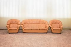Leather armchairs and sofa in interior of modern room Stock Photos