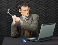 Comical person intends to break computer with hammer Stock Photos