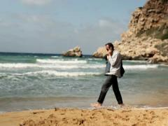 Businessman talking on cellphone and walking on the beach NTSC - stock footage