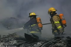 Firemen working on recycling facility fire 007 Stock Footage