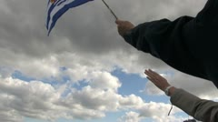 Netherlands Rotterdam arm waving small flag against clouds Stock Footage