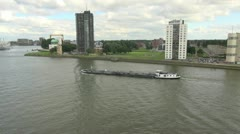 Netherlands Rotterdam barge passes riverfront apartments Stock Footage