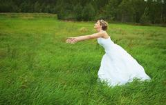 bride hastens towards to groom on meadow - stock photo
