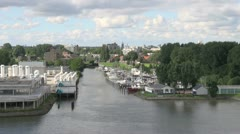 Netherlands Rotterdam tree lined harbor pan to cranes Stock Footage