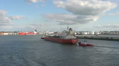 Netherlands Rotterdam red tanker and tug pass refinery 14a Stock Footage